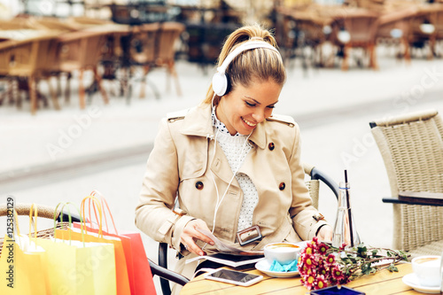 Young woman reading magazine in a cafe and listen music via head Poster
