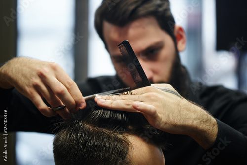 The Barber a man with a beard in the process of cutting the client a pair of sci Poster