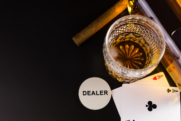 A glass of whiskey, a bottle, two aces, cigar,  and a dealer chip on black.