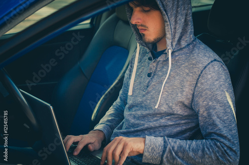 Poster hacker sit in car with his laptop