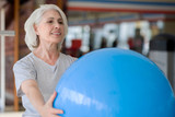 Smiling pleasant woman doing exercises with fit ball.