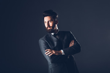 Young handsome bearded caucasian man posing indoors. Perfect skin and hairstyle. Wearing elegant jacket, jeans. Studio portrait with dramatic light.