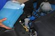 Mecánico llenando el depósito del líquido limpiaparabrisas del coche