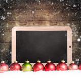 Weihnachtskugeln im Schnee mit leerer Kreidetafel