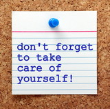 The words Don't Forget to Take Care of Yourself on a note card pinned to a cork notice board as a reminder to look after our own mental and physical health - 125521910