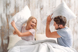 Fototapety Young man and woman playing with cushions