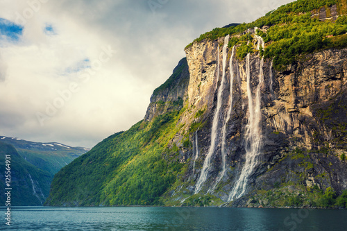Geiranger fjord. Seven Sisters Waterfall, Norway. Mountain landscape with cloudy sky. Beautiful nature.  - 125564931