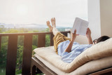 Rear view of asian man relaxing on a sofa and holding book on bed at home terrace with beautiful green background view. Relaxing concept. - 125585736