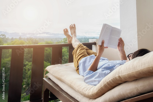 Wall mural Rear view of asian man relaxing on a sofa and holding book on bed at home terrace with beautiful green background view. Relaxing concept.