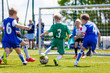 Leinwanddruck Bild - Football soccer match for children. Boys playing football game on a school tournament. Dynamic, action picture of kids competition during playing football. Sport background image.