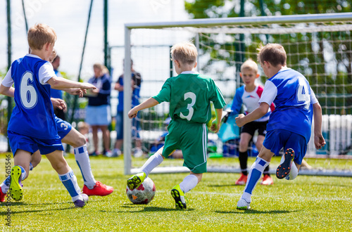 Leinwanddruck Bild Football soccer match for children. Boys playing football game on a school tournament. Dynamic, action picture of kids competition during playing football. Sport background image.
