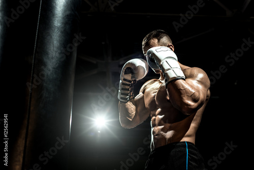 Poster boxer in gym with punching bag