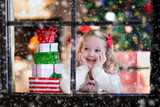 Fototapety Child watching out of window on Christmas eve