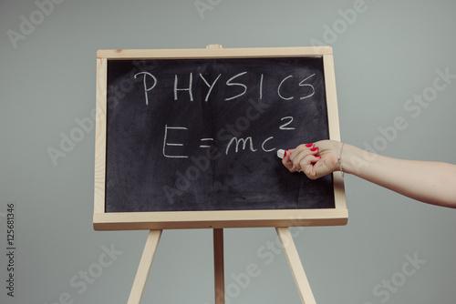 Poster Physics word and formula E=mc2 on chalkboard