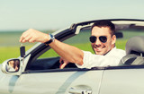 happy man in cabriolet showing car key