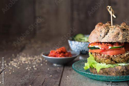 Foto Murales hamburger vegetariano con pane alle olive fatto in casa; verdure e salse in ciotole di ceramica. Sfondo rustico di legno. Spazio per scrittura