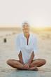 Молодая счастивая женщина в белой рубашке сидит на песке