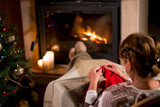 Grandmother knits a sweater sitting in front of fireplace