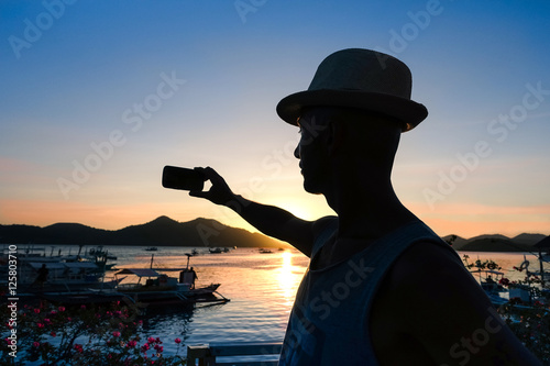 Travel man silhouette selfie at sunset with lagoon landscape