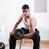 Man sitting on a chair and pumping the irons