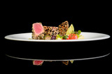 Tuna steak with vegetables on black background with reflection