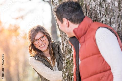 Poster Verliebtes junges Paar spielt verstecken im herbstlichen Park