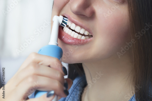 Close up of brushing teeth with electric toothbrush Poster