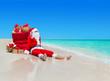 Christmas Santa Claus with gift boxes sack at tropical beach
