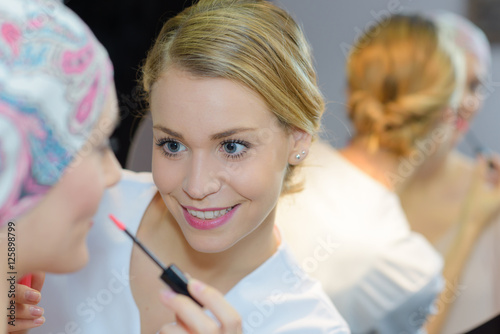 Beautician applying lipgloss to woman Poster