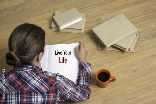 Woman reading book Live Your Life by stack of books Poster