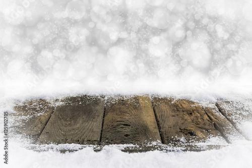 Alte Holzbretter im Schnee mit Bokehhintergrund