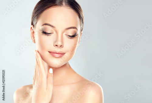 Leinwanddruck Bild Beautiful Young Woman with Clean Fresh Skin  touch own face . Facial  treatment   . Cosmetology , beauty  and spa .