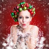 attraktive Frau mit Weihnachtshaarschmuck pustet Schneeflocken