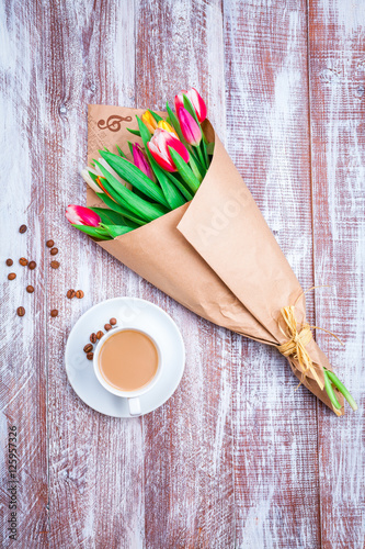 Poster the bouquet of tulips is wrapped in a paper isolated on a wood background