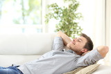Relaxed man resting on a couch at home - 125982757