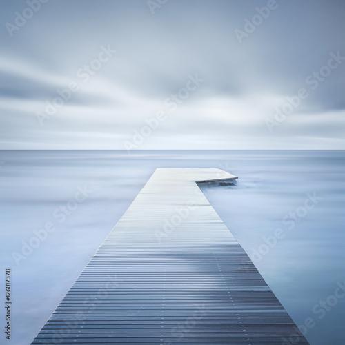 Obraz na Plexi Wooden pier, rocks and calm sea on long exposure.