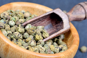 Green peppercorns in a bowl and wooden scoop