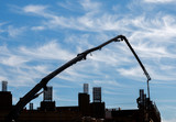 Construction site telescopic crane silhouette, sky and clouds background