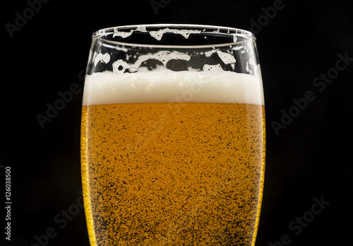 Poster glass of beer with bubbles and foam on black closeup.