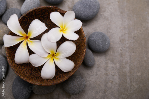 Fotobehang Spa Three frangipani in wooden bowl with spa stones on grey background.