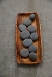 set of pile of stones in wooden bowl on grey background.