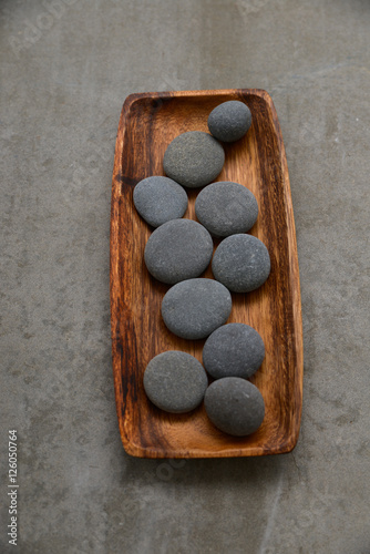 Poster Spa set of pile of stones in wooden bowl on grey background.