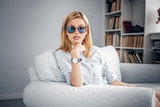 Portrait of blonde female in blue hipster sunglasses.