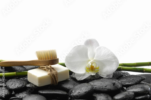 Poster Spa White orchid blossom with black stones ,grove,soap on wet background
