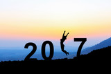 Silhouette young woman jumping over 2017 years on the hill at su