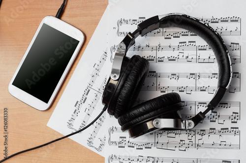 Audífonos con partitura y reproductor de música en escritorio de madera Poster
