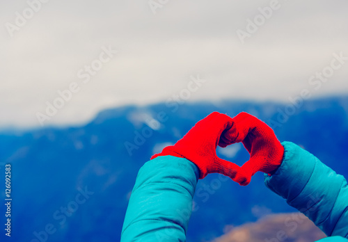 Poster hands in heart shape in winter nature. Love mountains travel