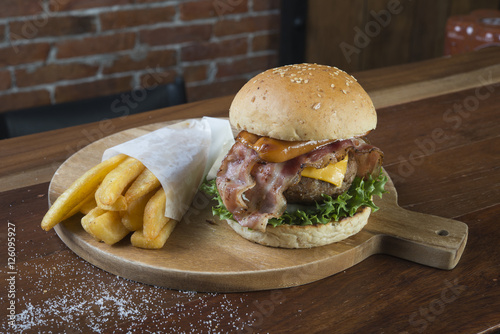 Poster Burger and french fries on wooden table