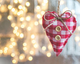 handmade heart Christmas decoration hands on a wooden branch on defocused Christmas lights background copyspace