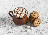 Hot chocolate with marshmallows and chocolate chips oatmeal cookies on a light background.
